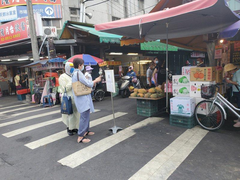 疫情升溫,街道人車都明顯減少,只是市場仍湧入不少買菜及雜貨的人潮,為避免成防疫破口,新北市場處和各區公所30日派人到各市場勸導及要求實聯制。 中央社