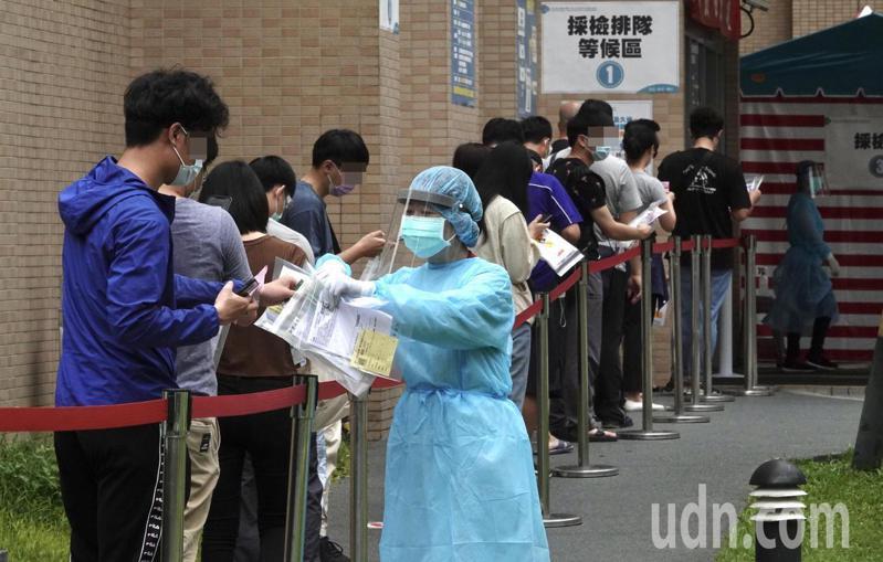 民眾排隊等候快篩,護理人員前送快篩資料。記者黃義書/攝影