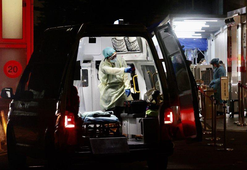 新冠疫情爆發,救護車載著一位又一位確診病患到醫院,醫護人員忙進忙出。記者許正宏/攝影
