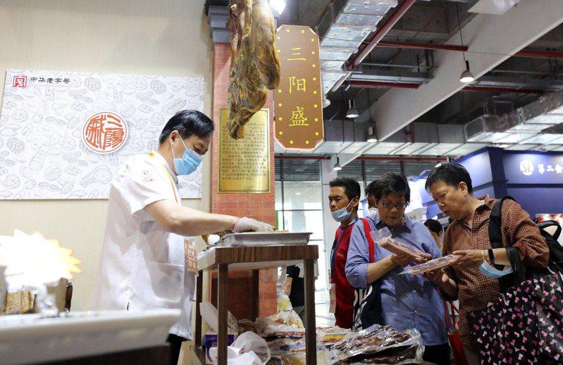 圖為參觀者在一家老字號展位前挑選肉類產品。(新華社)
