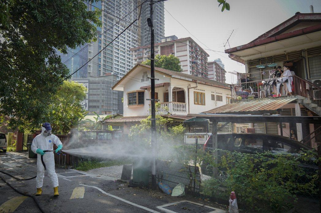 圖為2020年3月宣布封城之後,衛生官員在當地的住戶區噴灑消毒劑。 圖/歐新社...