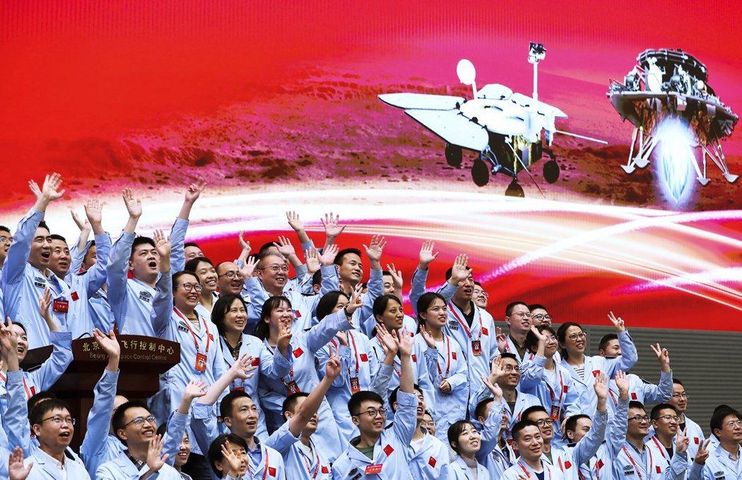 5月15日,北京航天控制中心的成員在天問一號探測器成功登陸火星後慶祝。 圖/美聯...