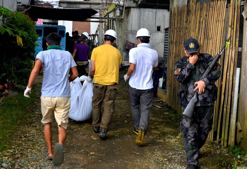 圖為2017年與馬巫德集團的衝突中,一群志願者抬走於路邊發現的一具屍體。 圖...