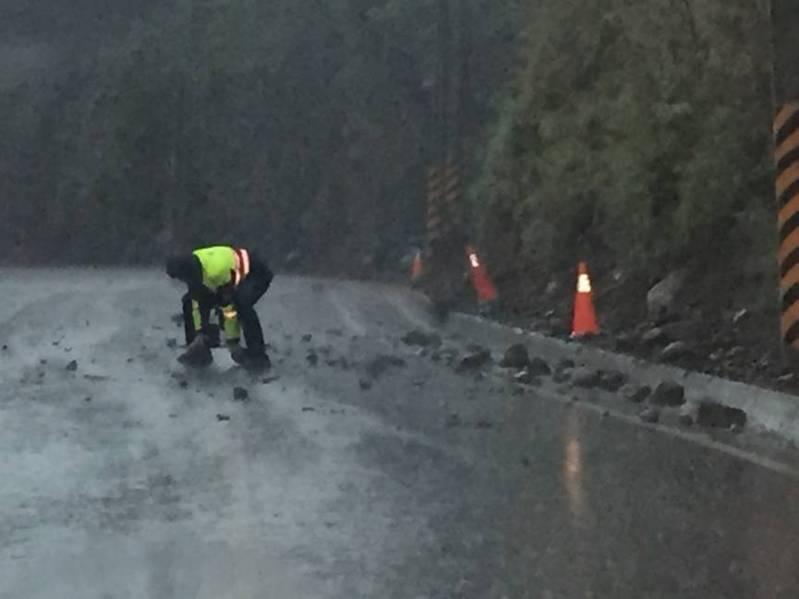 今天下午4時許,高雄台20線91公里處有落石掉落路面,員警冒雨徒手搬離落石。圖/民眾提供