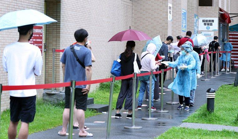 醫院醫護人員為大批排隊快篩民眾發放號碼牌。記者侯永全/攝影
