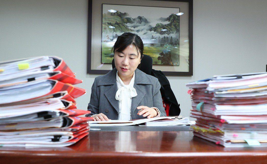 金融評議中心總經理洪令家的桌上擺滿等待評議的金融商品爭議案。 圖/潘俊宏 攝影