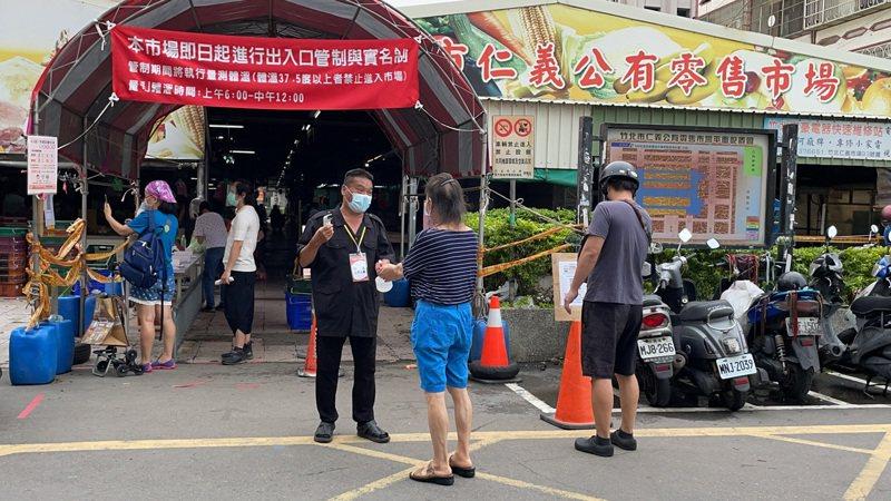 竹北市仁義公有零售市場出入口採單一管制,進入前須消毒、量體溫,並實施實聯制管理。記者陳斯穎/攝影