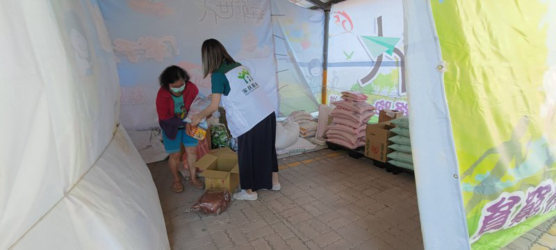 彰化家扶中心在戶外停車場搭帳蓬,讓受扶助家庭在外面領取物資。記者簡慧珍/攝影