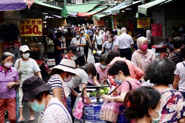 多個縣市已有不少確診個案都因採買物資確診,圖為台北市北投的傳統市場民眾戴上口罩防...