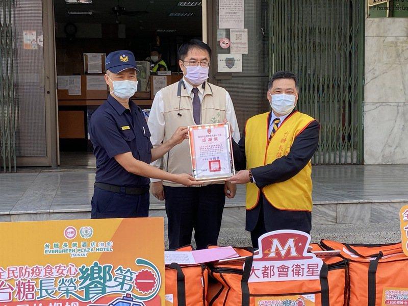 台糖長榮酒店總經理鄭東坡(右)贈送「防疫愛心餐盒」給台南市警一分局員警,由分局長方國璽(左)代表收下,市長黃偉哲(中)也到場慰勞員警。圖/台南市警一分局提供