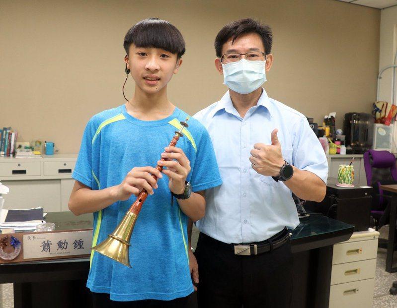 高雄市橋頭區興糖國小六年級重度聽障學生吳慕安(左)榮獲2021總統教育獎,校長蕭勳鍾(右)鼓勵。圖/高雄市教育局提供