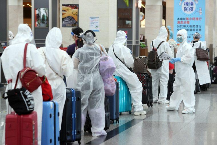 國內疫情嚴峻,圖為上午松山機場國際線爆滿,搭機民眾人人全副武裝穿隔離衣戴防護鏡防...
