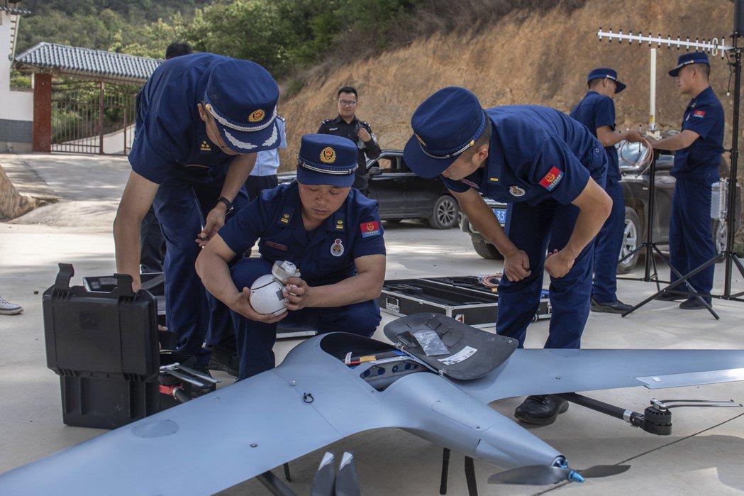 圖為5月29日,雲南省峨山縣的一群消防隊員們準備無人機來觀測象群,附近居民已被疏...