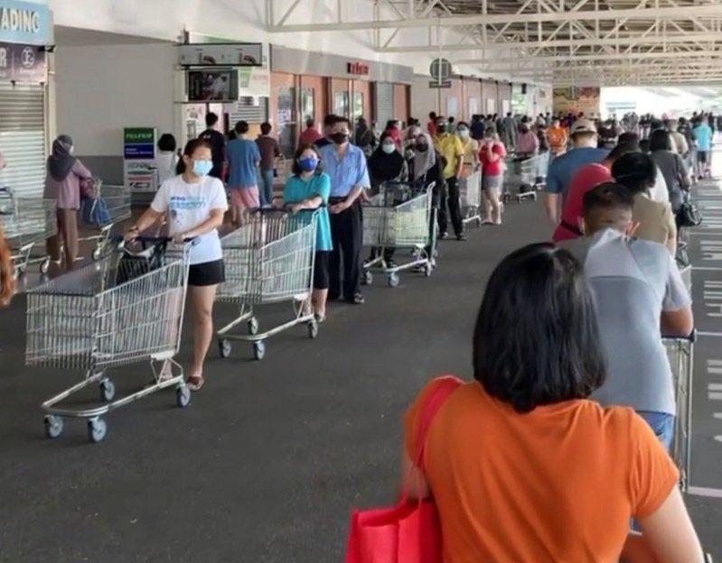 馬來西亞宣布全國封城後,超市出現大量排隊搶購人潮。(路透)