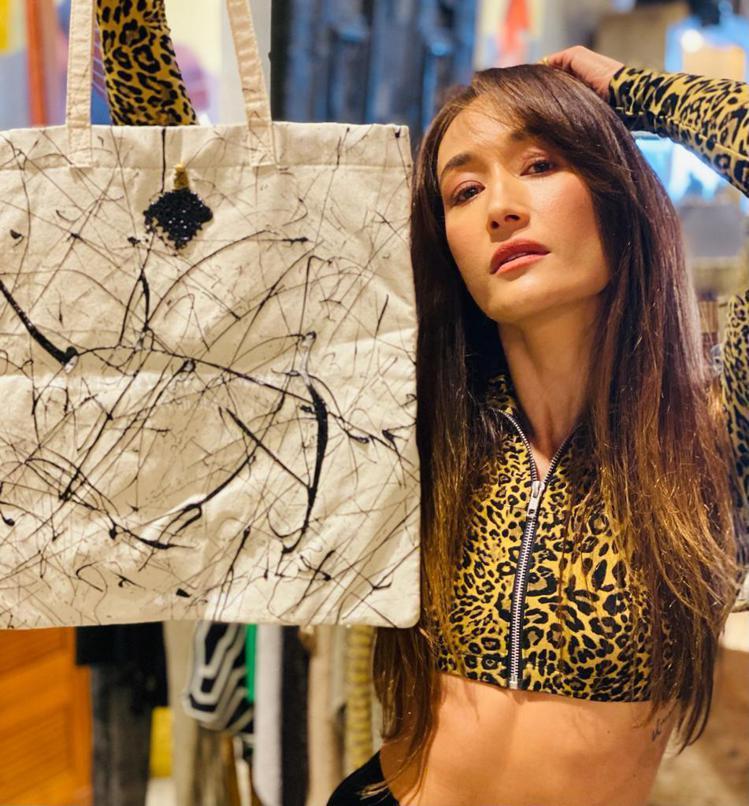 香港出身的Maggie Q及她為此次慈善拍賣創作的托特包。圖/佳士得提供