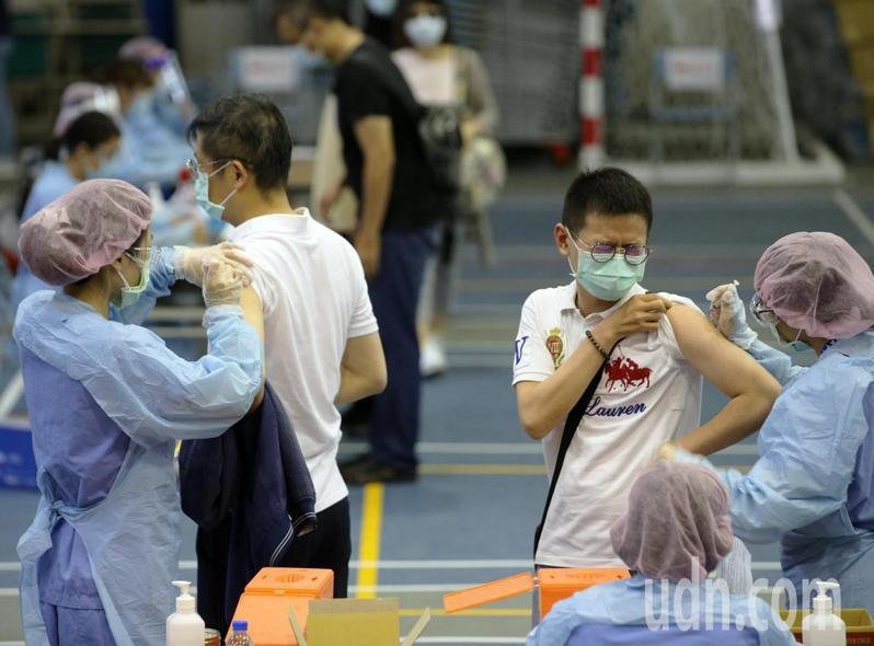 高雄設置大型疫苗注射站,今天上午就有第一線的醫護人員到三民家商排隊等待注射AZ疫苗,工作人員排出防疫距離動線,並且加快施打流程。記者劉學聖/攝影