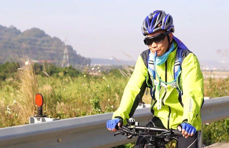 邱大信因罹患鼻咽癌,需背著水袋不斷喝水,但他堅持完成自行車環島募款。 圖/邱大信...
