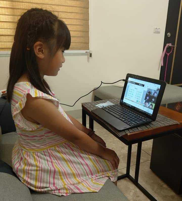 在家防疫期間,陪孩子線上教學。
