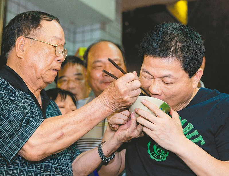前立委顏清標(右)2014年6月6日假釋出獄,顏的爸爸(左)親自餵吃豬腳,希望能去除霉運。圖/聯合報系資料照片