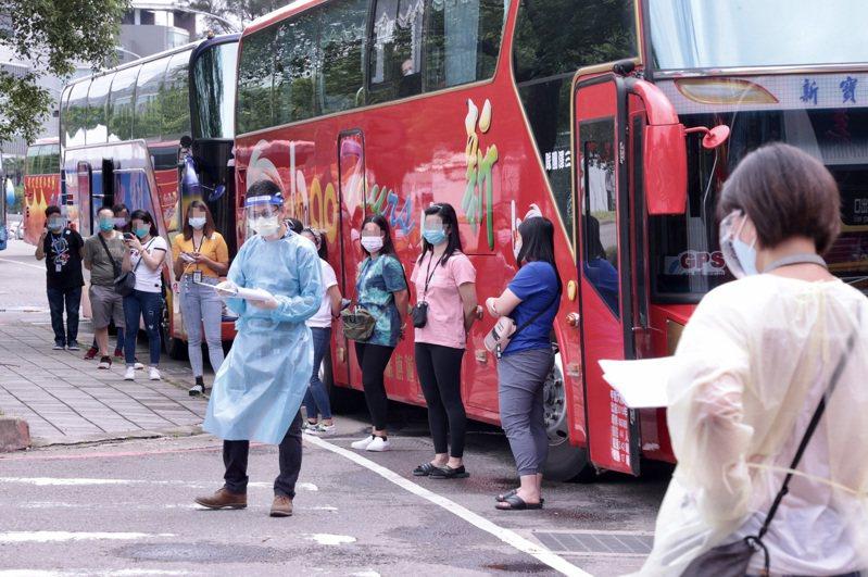 移工搭乘遊覽車到新竹科學園區「快速篩檢站」,等待分批進入。記者黃義書/攝影