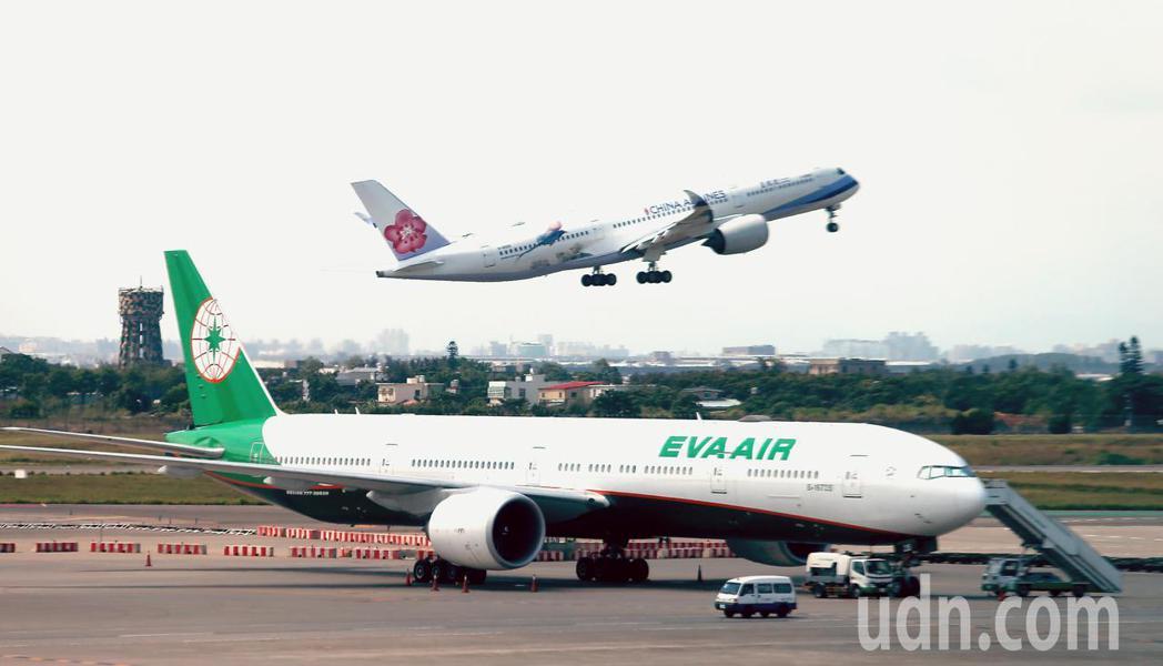 長榮航空公司停放在桃園機場第二航廈的波音777-300ER客機,後方為起飛中的中...