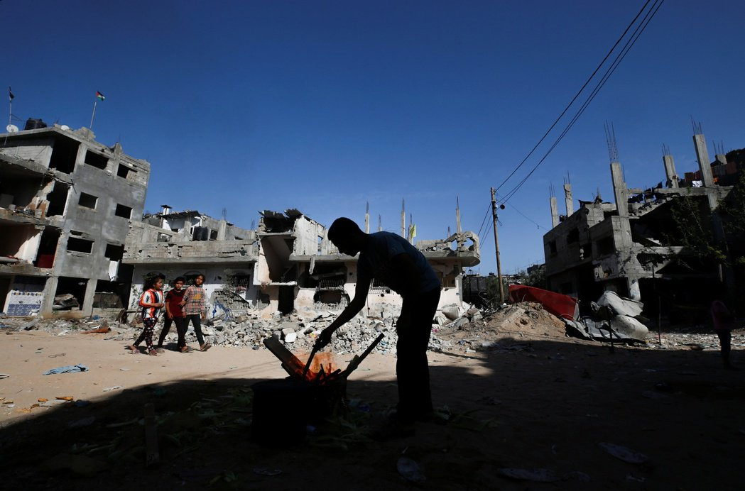 攝於6月9日,一名巴勒斯坦人在被摧毀的平房中烹煮玉米。 圖/路透社