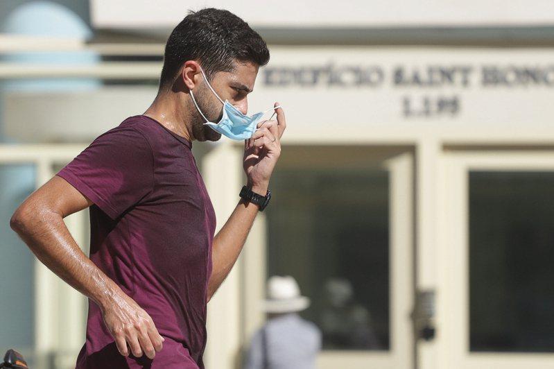 圖為巴西聖保羅市一名男子戴口罩在街頭跑步。 新華社