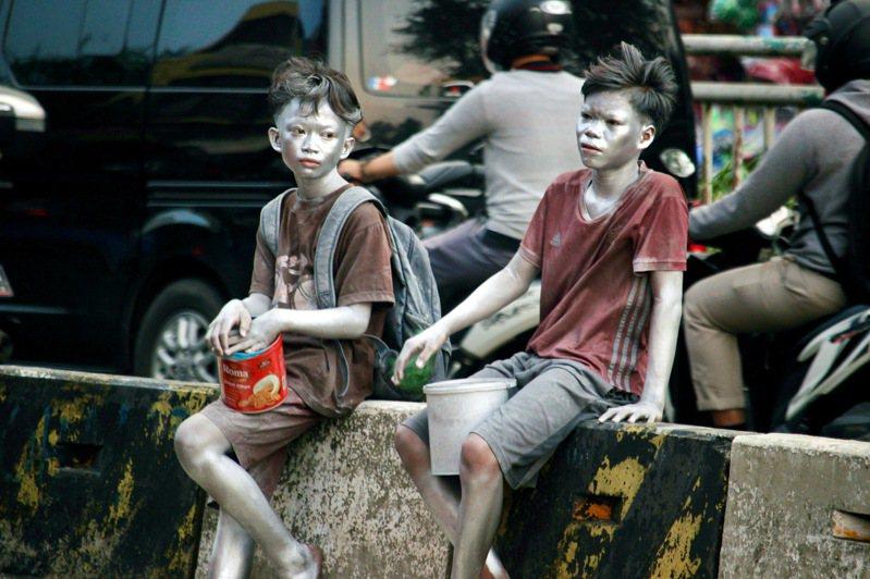 住在雅加达东区的南昂(左)在就学之余,与朋友在街头当「小银人」,帮父母赚取家用。图摄于5月19日。中央社(photo:UDN)