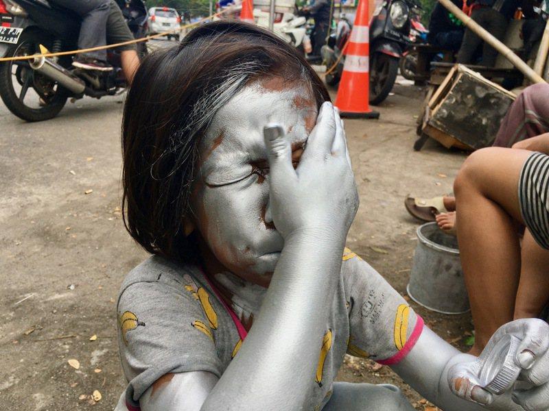 雅加达东区常见在街头当「小银人」的孩童,他们说,父母亲不反对他们工作,学校也知道,只希望他们不要忘记课业。图摄于5月21日。中央社(photo:UDN)