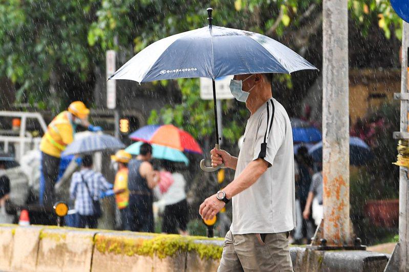 台北街頭民眾撐傘遮雨。中央社