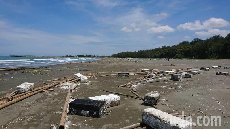 台南市安平區漁光島海灘滿布支離破碎的蚵架、竹子與浮具,美麗沙灘變色。記者鄭惠仁/攝影