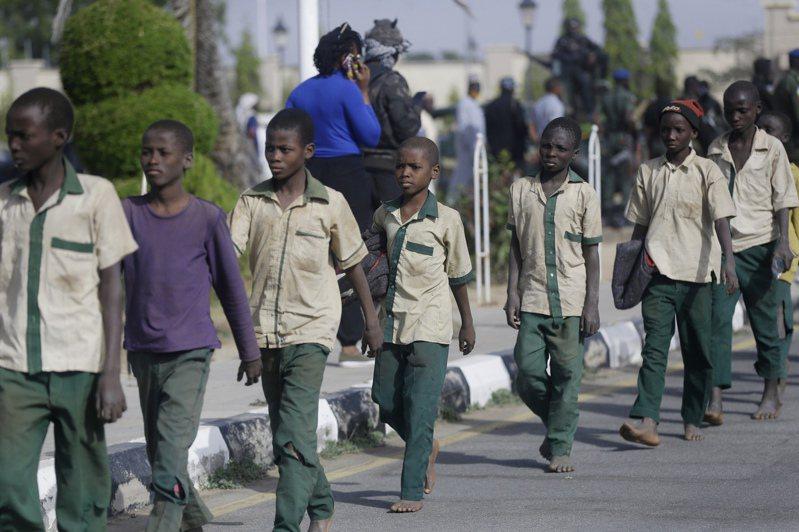 奈國北部卡齊納市被綁架的一批男學童去年12月18日獲釋後,在軍方和政府官員護送下前行。美聯社