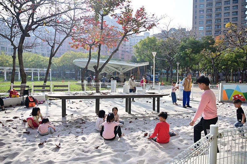 整潔寬敞的遊戲沙坑區,外圍設置白色抿石子座椅及白色防護圍籬,避免動物進入沙坑造成汙染,並規劃沙桌,讓各年齡族群皆可共同玩沙。(圖片提供/高市府養工處)