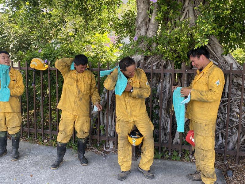 上個月底,玉山高山火災現場回來的森林護管員,用乾淨的毛巾擦拭身體,清掃一身疲憊,工作並不輕鬆。圖/林務局提供