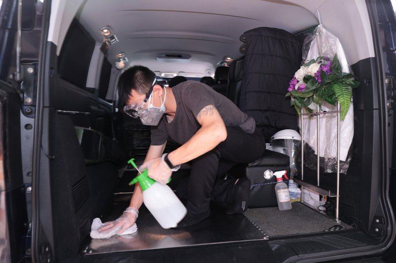 本土疫情下死後確診案例,成為第一線接體員的風險,防護設備也因大量消耗,面臨不足的危機,圖為接體員為車輛清潔消毒。記者黃義書/攝影