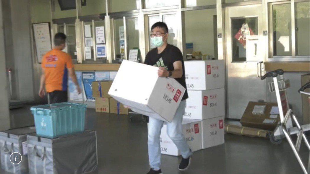 衛生局人員小心翼翼的搬運AZ疫苗,希望將疫苗安全的送抵儲存地點。記者蔡家蓁/攝影