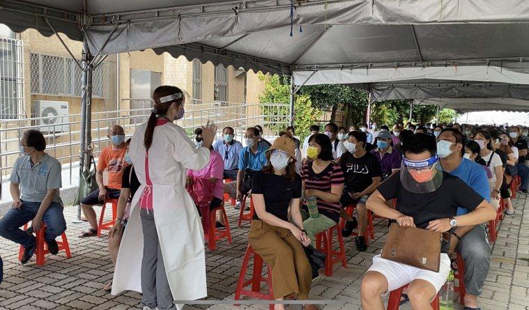 台南市大型疫苗注射站今天開打,圖為東區復興國中注射人員向排隊民眾說明情況。記者修...