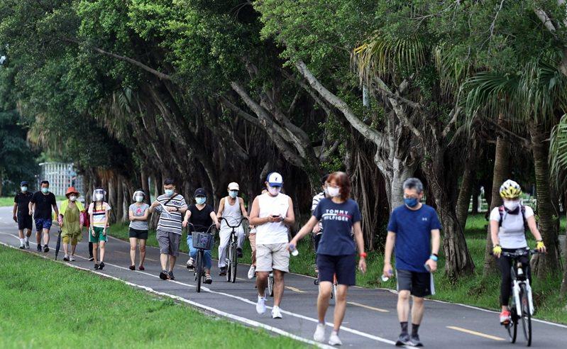 端午連假第二天,不少民眾戴著防護面罩及口罩到新店溪畔的河濱公園散步或騎乘單車。記者侯永全/攝影