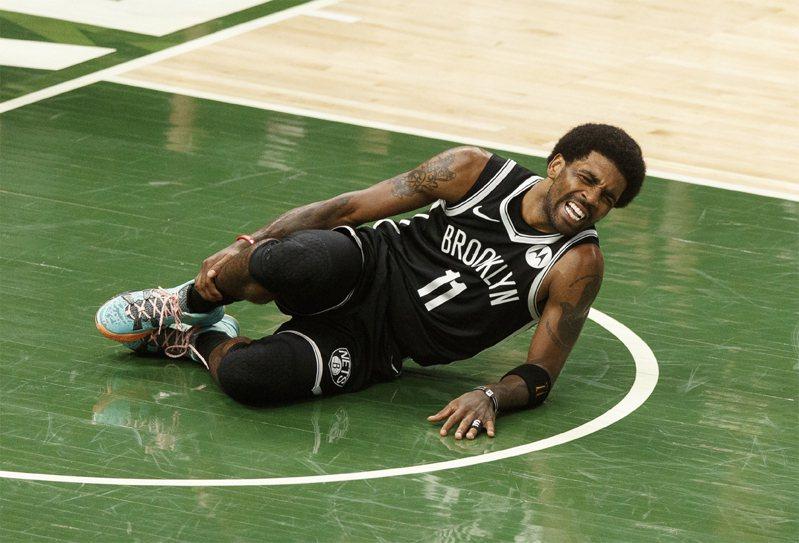 籃網球星厄文在上半場,不慎絆到安特托昆博的腳後倒地,表情痛苦。路透
