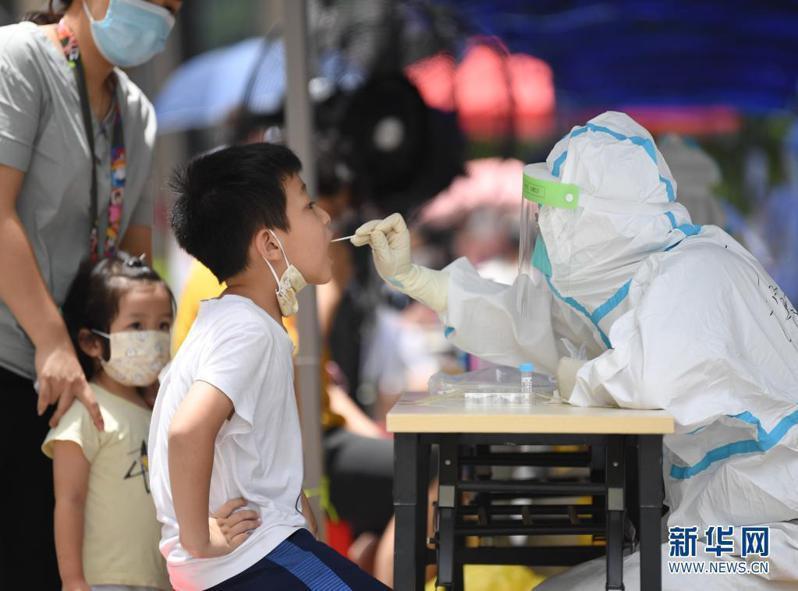 廣州在傳出本土新冠疫情後,隨即展開大規模核酸篩檢。圖為廣州荔灣區醫護人員12日為孩童進行核酸檢測採樣。(取自新華網)