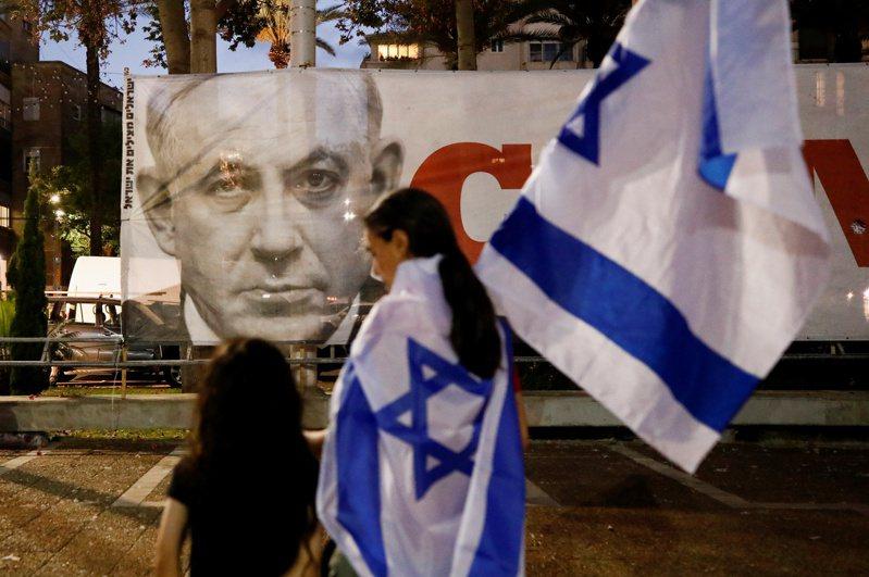 支持以色列新政府的民眾13日披著國旗,經過特拉維夫街頭一幅前總理內唐亞胡的圖像。路透