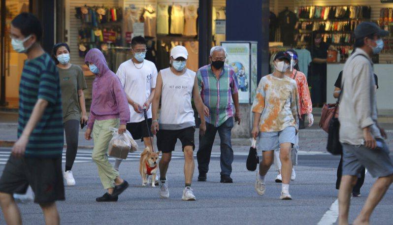 端午假期已過,疫情似乎有趨緩的現象,來看雙北各區最新確診人數變化。圖為台北街頭民眾配戴口罩防疫情形。美聯社