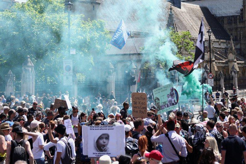 反對防疫封鎖的民眾十四日聚集在倫敦英國國會大廈外,抗議首相強生將宣布延後解封。(路透)