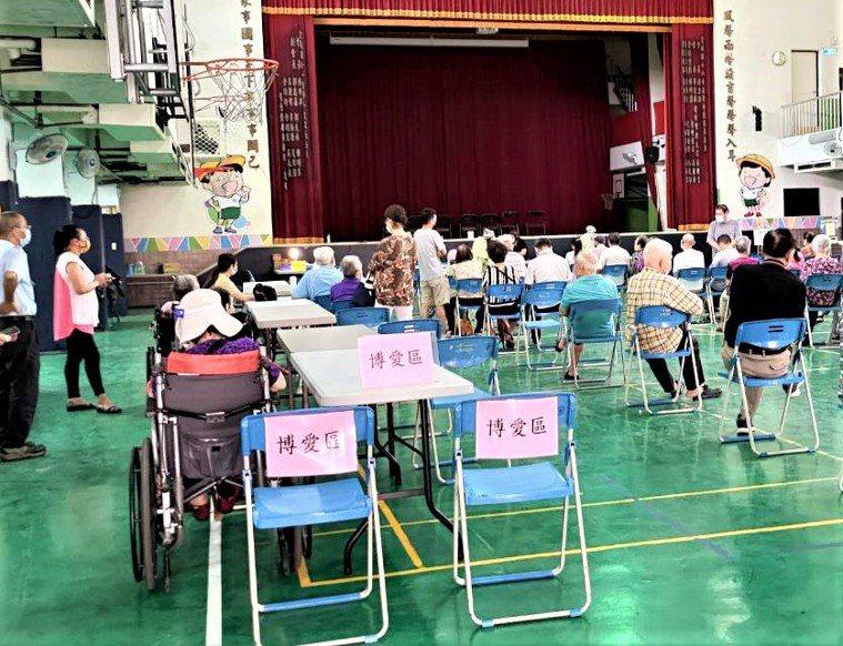 台中市塗城國小開設疫苗快打站,怕老人家坐不穩,還特別設了「博愛區」並放上大桌子,...