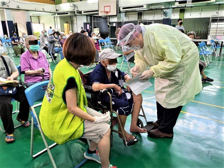 台中市塗城國小開設疫苗快打站,老師們(左)空上黃背心服務老人家。圖/民眾提供