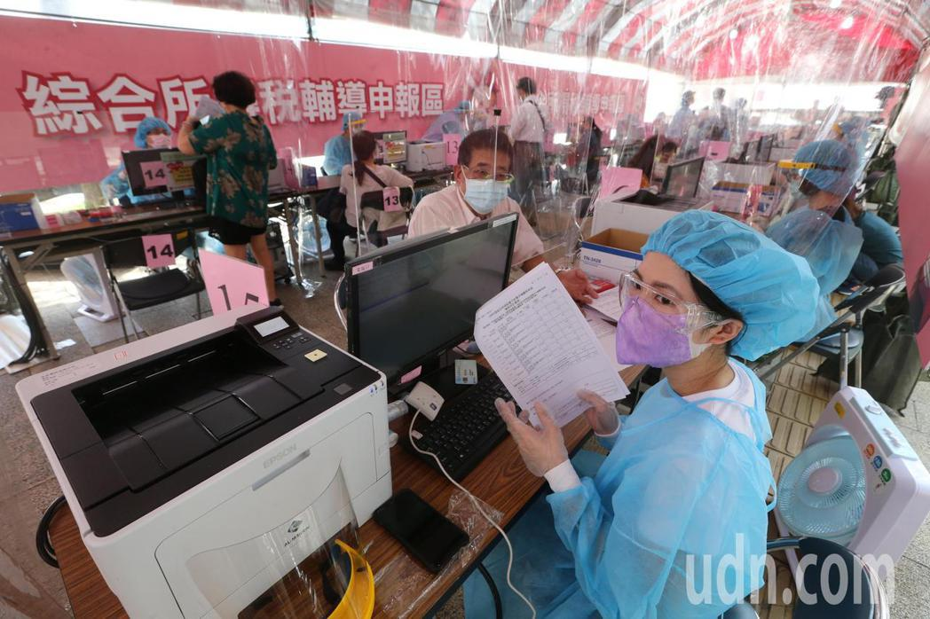 國稅局自今天起開放民眾臨櫃報稅,採預約制並限制人數,在台北國稅局,稅務人員穿上防...