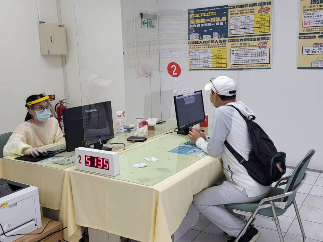 高雄市國稅局今首日開放臨櫃報稅,服務人員與民眾間有隔板隔開。記者蔡孟妤/攝影