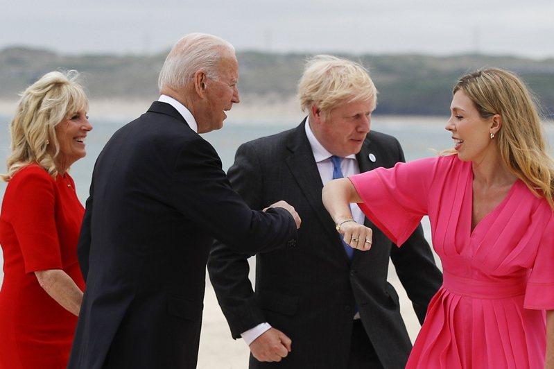 英國首相強生夫婦(右)11日在英國康瓦爾郡卡比斯灣,與到訪的美國總統拜登夫婦親切打招呼。美聯社
