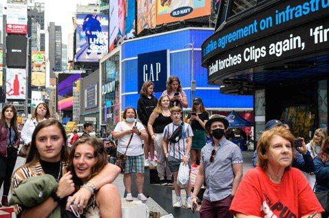 當疫情持續嚴峻,人們的防禦心反而降低。圖為在美國紐約時代廣場看表演的人群。 法新...
