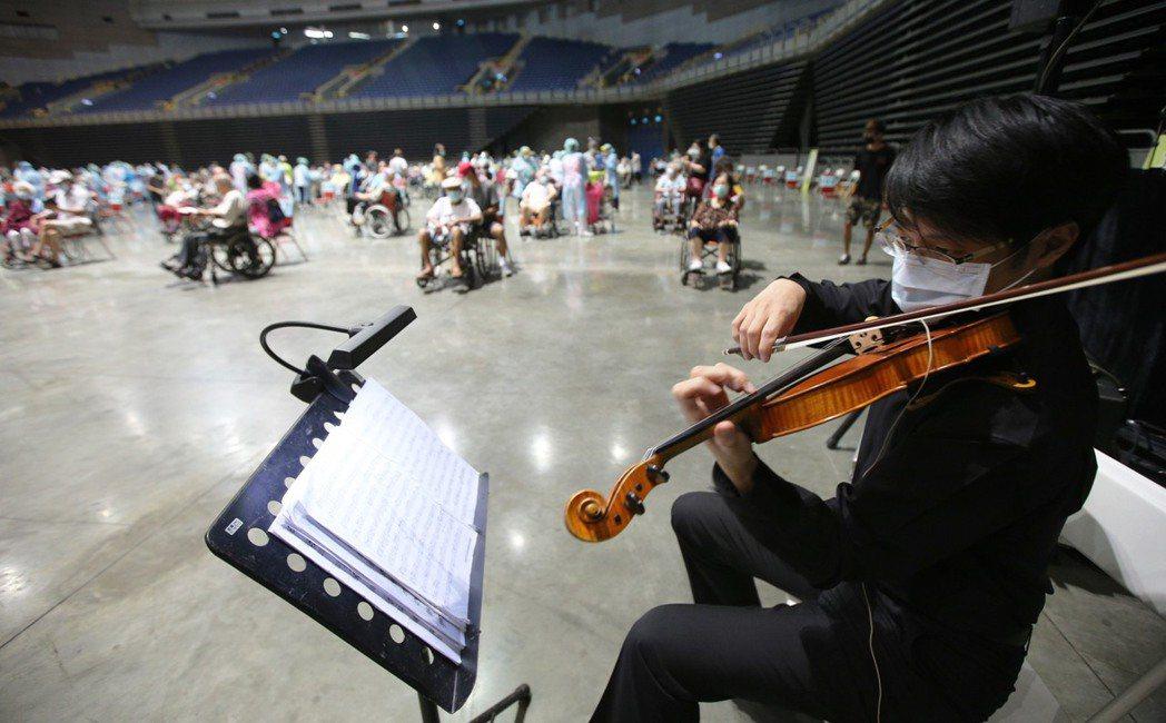 為紓解大型接種站緊張氛圍,高雄市政府安排音樂表演。記者劉學聖/攝影